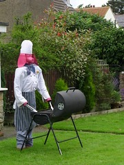 Barbie pig (Nekoglyph) Tags: appletonwiske yorkshire village scarecrow festival 2017 summer pig pink barbeque bbq barbie chef apron stripes garden trees hedges green blue grass spatula cooking roofs barbecue