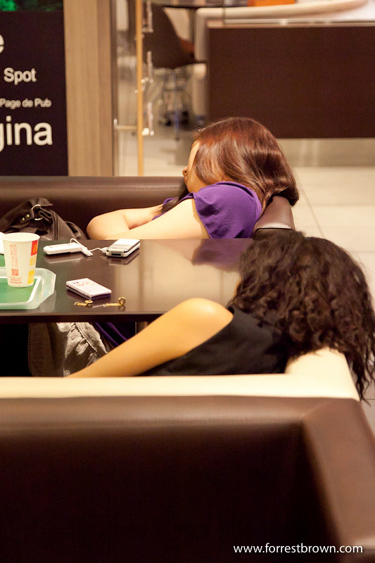 Person sleeping in a Japanese fast food restaurants.