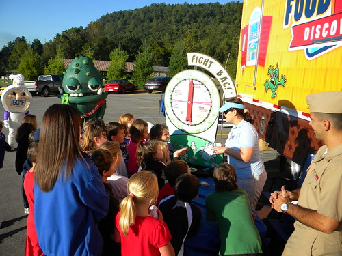 Eastern Kentucky school children react enthusiastically to the hero, Thermy™ and BAC!® the villain at the USDA Food Safety Discovery Zone.
