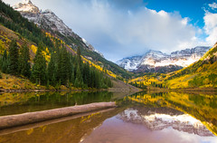 Maroon Bells (Jim Boud) Tags: camera wood blue autumn sky brown mountain snow reflection green fall water leaves yellow clouds sunrise canon landscape eos leaf log colorado dof cloudy wideangle depthoffield rockymountains shallow aspen dslr digitalrebel photoart digitalslr firtree waterscape maroonbells artisticphotography superwideangle canon1022mm maroonlake jimboud t2i jamesboud eos550d kissx4