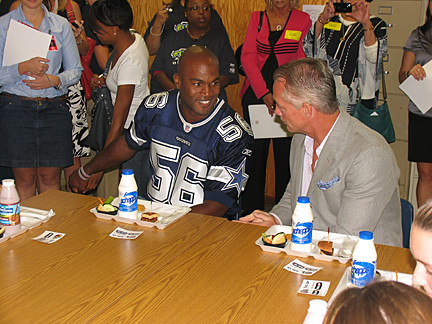 "Bradie James, linebacker for the Dallas Cowboys, and Daryl ""Moose"" Johnston, former Dallas Cowboys player, taste-tested some new food with students at Dealey Montessori Vanguard and International Academy in Dallas."