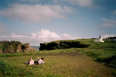 (kara o'keefe) Tags: ocean girls sea cliff lighthouse film grass clouds newfoundland picnic path bluesky catherine blanket kaitlyn bellisland jillwillcott
