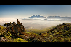 View from the top... (Chantal Steyn) Tags: africa road travel blue sky panorama plants sunlight mist mountains tree tourism rock fog clouds landscape southafrica highway view capetown panoramic vegetation farms fynbos westerncape nohdr winter2010 sirlowriespass n2highway chantalsteyn winter2010finalist wwwcapetowntravel