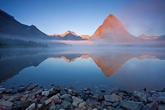 Swiftcurrent Lake Sunrise (Matt Champlin) Tags: life morning camping summer mist lake snow mountains reflection misty fog sunrise canon landscape photography dawn photo amazing cool montana rocks foggy scenic nopeople hike glacier snowcapped glaciernationalpark alpen majestic tranquil isolated alpenglow 2010 grinnell swiftcurrent manyglacierhotel swiftcurrentlake manyglacier grinnelpoint mywinners abigfave mountgould eos40d montanalandscape montanascenics swiftcurrentlakesunrise