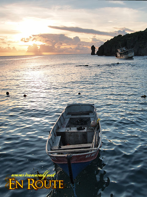 Boats, cliffs and shipwreck seen from Basco Port