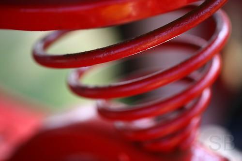 red tractor abstract blur minnesota metal circle spiral spring state loop bokeh background seat machine fair machinery curly loopy curl mn minnesotastatefair 2007 diameter decreasing studiobaker