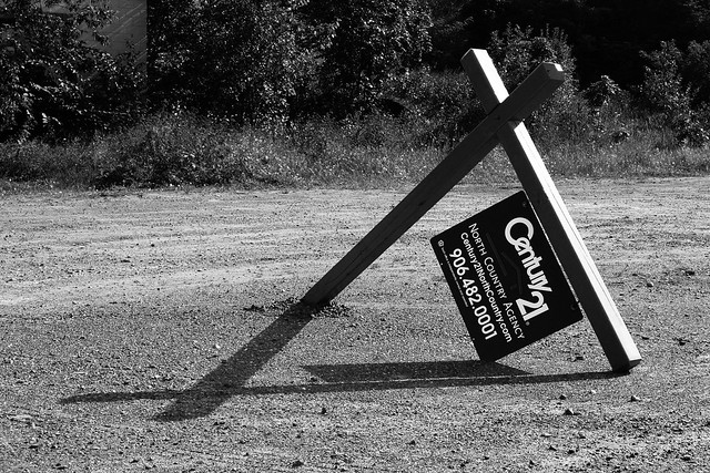 A for sale sign, fallen down.