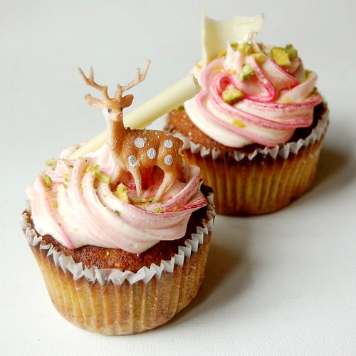 pistachio cupcakes w. white chocolate & rose frosting, white chocolate curls, miniature deer & pistachio dust.