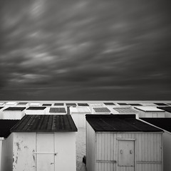 Dark rainclouds and beach houses - Calais, France 2010 (Joel Tjintjelaar) Tags: france beach calais bwphotography cabins beachhouses daytimelongexposure nd110 blackandwhitelongexposure silverefexpro tjintjelaar bwnd11010stopsfilter frenchseascapes