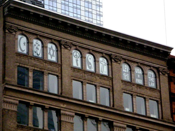 a brick New York apartment building. In each of the top floor windows, a different religious symbol is placed to spell out COEXIST overlooking the Ground Zero site.
