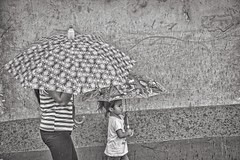 textures and umbrella patterns in B&W (Pejasar) Tags: girl woman mother daughter child rain antigua guatemala textures patterns wall umbrellas walk candid street bw blackandwhite