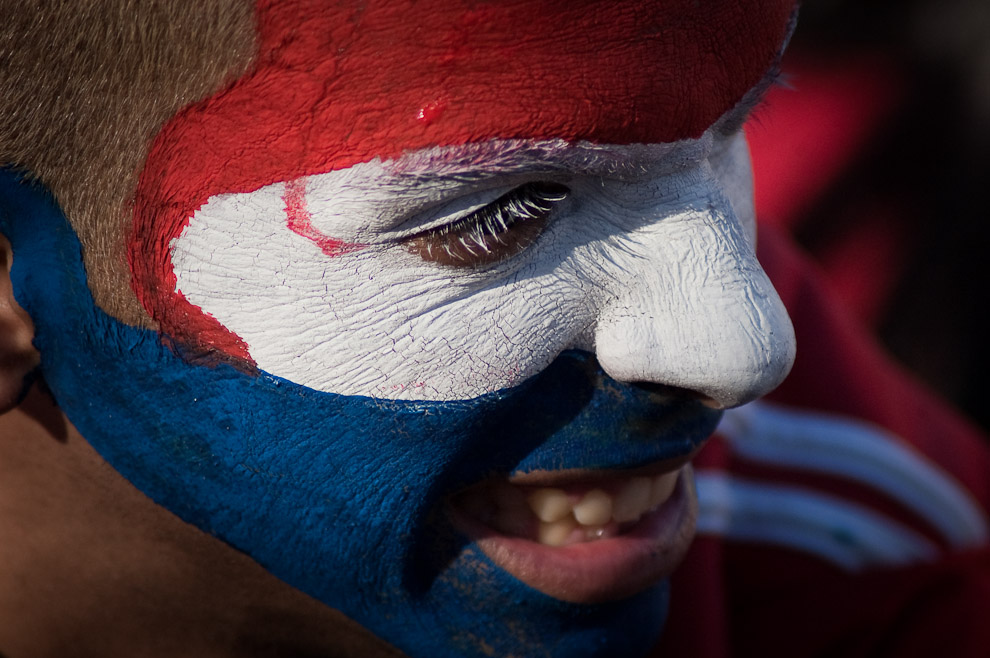 Un hincha Paraguayo se pinta el rostro con los colores de la bandera Paraguaya en la Plaza de la Democracia (Elton Núñez - Asunción, Paraguay)