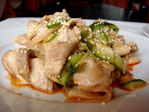 Thin slices of cooked pork intermingled with equally-thin slices of cucumber, piled on a white plate and drizzled with finely-minced garlic in chilli oil.  White sesame seeds are scattered over to finish.