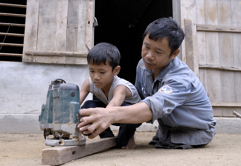 Mr. Son and his son Tran Xuan Lam working with the power saw