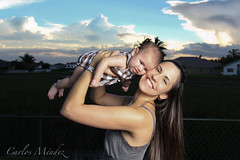 Like Mother, Like Daughter (biggcstylez) Tags: family sunset summer sky baby cute colors beautiful smile face clouds umbrella canon eyes expression wide emma wideangle sylvia 2010 lightroom speedlite 1740f4l offcameraflash 50d strobist canon50d 580exii 430exii speedlite430exii photoshopcs5