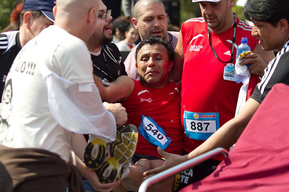Jorge Luis Quie es auxiliado por los paramedicos luego de caer al suelo momentos después de cruzar la meta luego de correr durante 4 horas y 11 minutos. Es natural que algunos competidores experimenten fuertes calambres después de terminar sus largas carreras.  (Tetsu Espósito - Asunción, Paraguay)