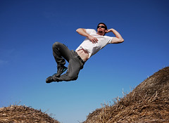 the relaxed way to jump on hay bales (ssj_george) Tags: camera blue sky people white man male shirt rural lens lumix person glasses jump jumping shoes village pants action air straw cyprus nike panasonic micro fields series rolls midair pancake 20mm hay burst bales leap dmc highspeed 43 larnaca fastshutter f17 gf1 continuousshooting mazotos  georgestavrinos   ssjgeorge