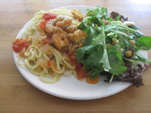 Linguini in white wine sauce with shrimps and tomatoes, salad