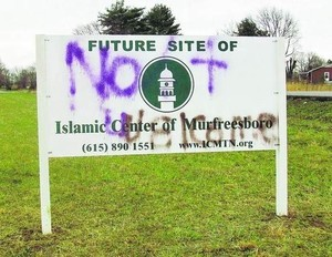 a roadsign that says Future site of Islamic Center of Murfresboro has been graffitted over to read Not Welcome