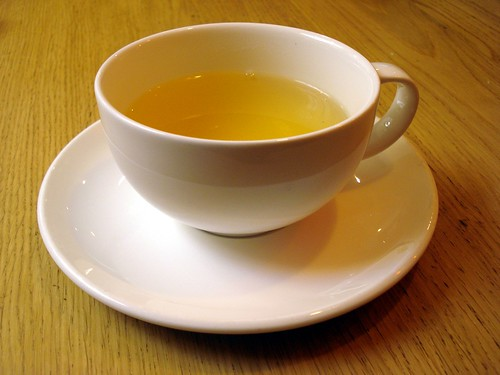 A white porcelain cup on a matching saucer, about two-thirds filled with a clear, honey-coloured green tea.