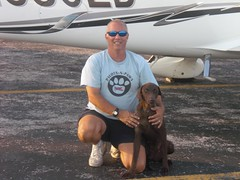 Pilots N Paws volunteer posing with a dog in front of a plane