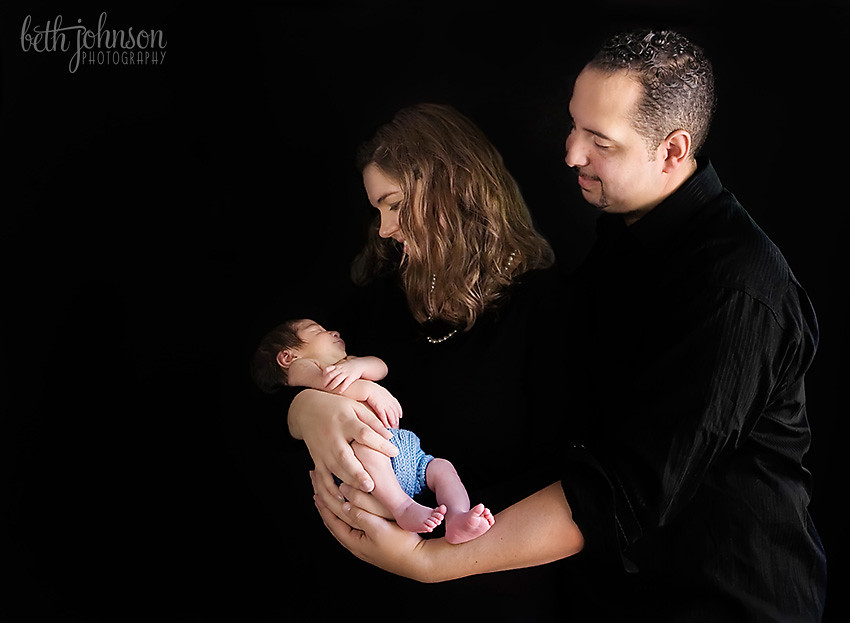 newborn baby with parents on black background