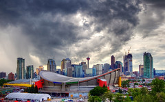 Skyline Over the Calgary Stampede (Jim Boud) Tags: photomatixhdr travel white jimboud jamesboud hdr highdynamicrange multipleexposures blendedexposure photomatix t2i dslr digitalslr digitalrebel eos eos550d kissx4 canon building skyscraper landmark skyline tower cityscape hotel northamerica clouds cloudy partlycloudy colorful blue red grey gray photoart artisticphotography dome stormyskies photoshop layers sky observatory bright light shine landscape crane canada calgary alberta stampede saddledome pengrowthsaddledome rodeo calgarytower province western 550d 1022mm canonefs1022mmf3545usm usm efs wideangle superwideangle 10mm 22mm canadian stadium lightrays sunbeams raysoflight sunrays