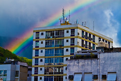 7AM, sun and a little bit of rain (daniel_gafanhoto) Tags: morning blue red brazil sky orange cloud green window rain rio yellow riodejaneiro clouds sunrise buildings rainbow colorful cityscape purple dusk cyan reflexion antenna tijuca