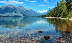 Along the Shoreline (Jeff Clow) Tags: trees summer vacation lake mountains reflection water landscape montana rocks quiet shoreline peaceful serene glaciernationalpark 2010 purity lakemcdonald mywinners anawesomeshot lakemcdonaldglaciernationalpark