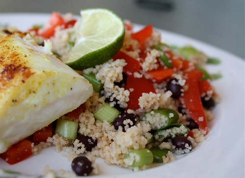 plate of couscous with green onions, black beans, red pepper, and a lime slice with adobo seasoned red snapper