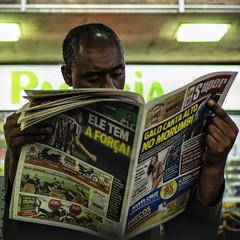 Super (AdrianoSetimo) Tags: newspaper jornal leitor reader belohorizonte rodoviária em10mkii olympus olympus25mmf18 mzuiko25mm18 downtown candid street streetphotography square 11 portrait hcsp