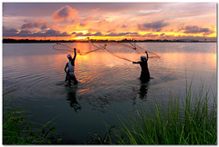 in tandem (Soumya Bandyopadhyay) Tags: sunset sky lake fish color net water clouds landscape fisherman dusk wide canon1785mmis gradnd canoneos40d