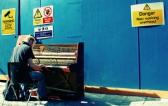 Image of a man playing a tired old piano in front of a building site that has warning signes.  One says, 'danger, men working overhead'.