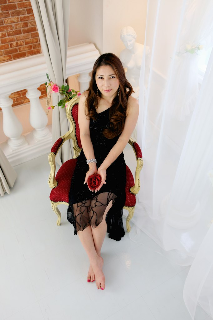 Japanese woman wearing black dress sitting in red and gold chair holding red rose looking up at camera