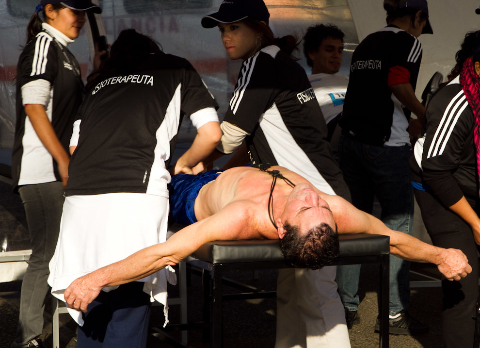 Un atleta recibe masajes luego de terminar la carrera a manos de fisioterapeutas mujeres en uno de los toldos de atención medica.  (Tetsu Espósito - Asunción, Paraguay)