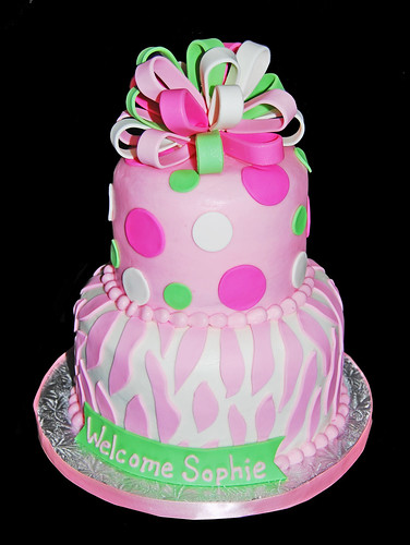 pink and green zebra print and polka dot baby shower cake topped with a mutlicolored bow