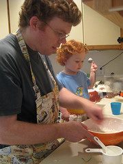 Speck helping Daddy do some baking, complete with aprons and measuring spoons