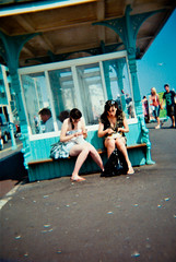 Eating Chips in a Seaside Shelter (AndyWilson) Tags: girls film 35mm seaside brighton candid toycamera chips promenade shelter 100asa sintex polaroidbranded sintexpalmcamera