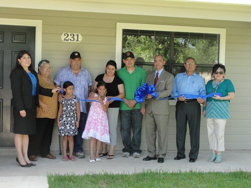 The Reanna Fernandez family proudly cuts a ribbon symbolic of starting their new life in a home they helped construct.  (State Director Paco Valentin is third from the right.)