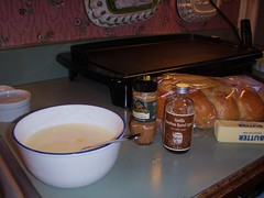 ingredients for out french toast, eggs in a bowl, milk, butter, cinnamon, vanilla bread all on the counter