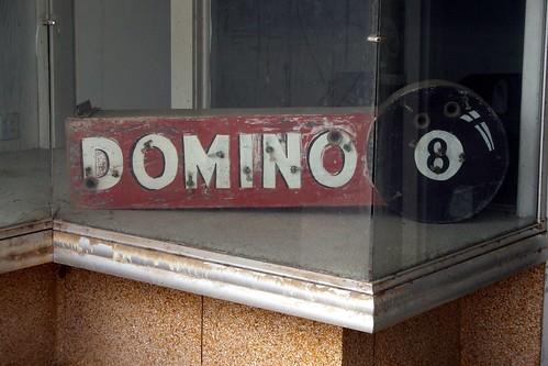 domino neon sign in carlton's shoe store window