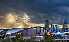 Sunbeams Over the Calgary Stampede (Jim Boud) Tags: travel blue light red sky white canada building calgary tower skyline clouds skyscraper photoshop canon landscape eos grey hotel is saddledome colorful cityscape shine bright cloudy crane stadium gray wideangle landmark canadian observatory alberta dome western northamerica rodeo layers usm dslr sunrays 1785mm digitalrebel photoart digitalslr efs1785mmf456isusm province stampede sunbeams calgarytower lightrays raysoflight artisticphotography partlycloudy stormyskies imagestabilization pengrowthsaddledome imagestabilized 550d jimboud t2i topazadjust jamesboud eos550d kissx4