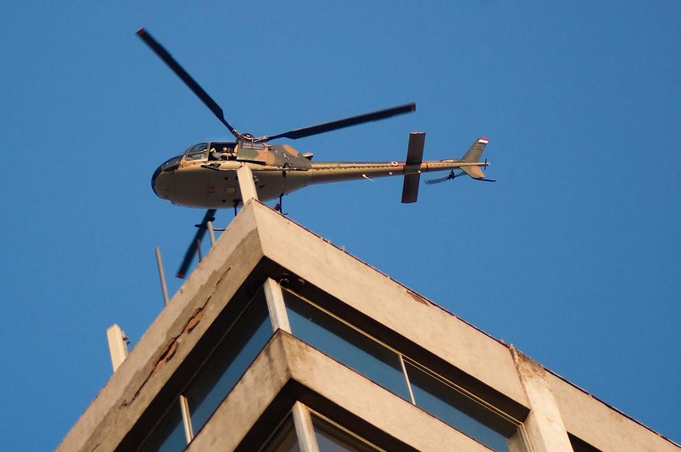 Un helicoptero Bell UH-1H de la Fuerza Aérea Paraguaya sobrevuela el techo del edificio Zodiac en su mision de proveer vigilancia desde el aire. (Elton Núñez - Asunción, Paraguay)