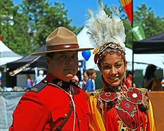Odd Couple (gordeau) Tags: red lady couple bc native britishcolumbia feathers surrey gordon rcmp colourful thumbsup mountie mountedpolice hollandpark ashby flickrchallengegroup flickrchallengewinner surreyfusionfestival gordeau