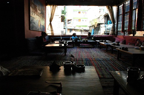 Friends chatting, Cool funky OR2K Restaurant, low tables, futons, wide open huge windows, Kathmandu, Nepal by Wonderlane