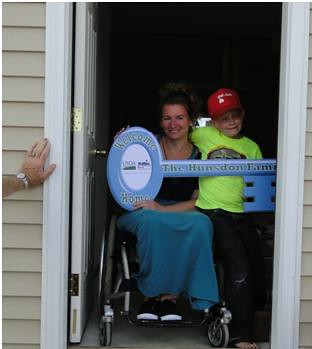 Valerie Hunsdon and her son Travis in the doorway of their new home.