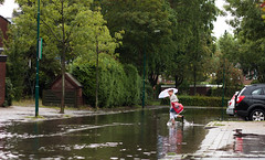 Walking on Water (MasterWillems) Tags: road blue red green water rain yellow kids cycling jumping fload splashes carspeople floaded