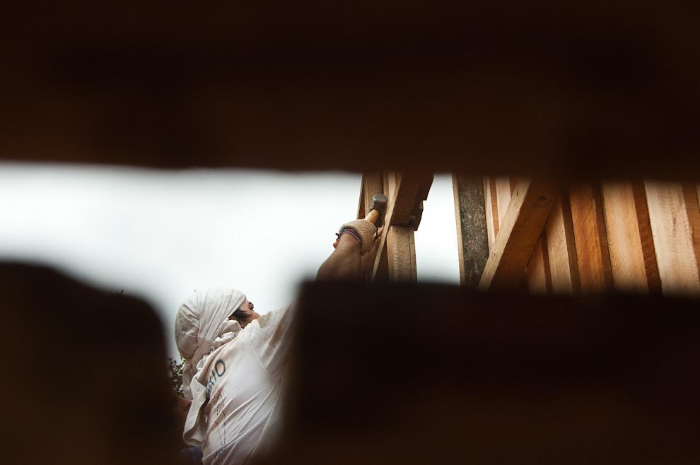Un voluntario esta clavando una de las vigas que forman el soporte para el techo de chapa en la construccion de un hogar del barrio Yukyty del Bañado cerca de Lambaré. (Elton Núñez - Asunción, Paraguay)