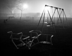 Playtime (pandawizard) Tags: blackandwhite bw playground fog dark prime weird scary play pentax 14 swings roundabout foggy sigma creepy ist atmospheric ds2 30mm sigma20mm pentaxistds2