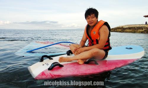 casey sitting on windsurf board